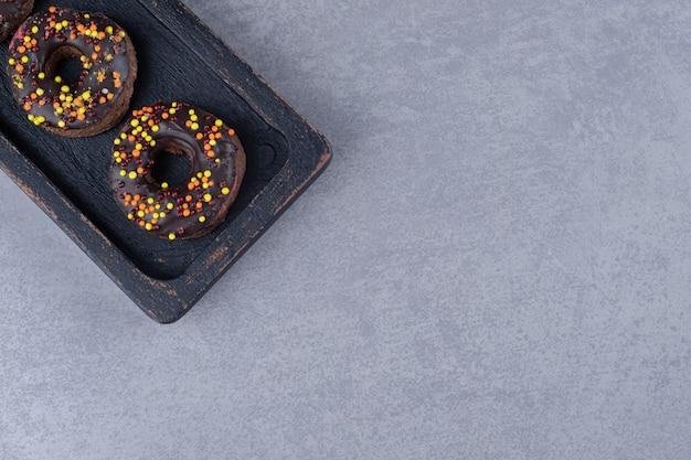 Chocolade en bestrooid snoep gecoate donuts op een schotel op marmeren oppervlak