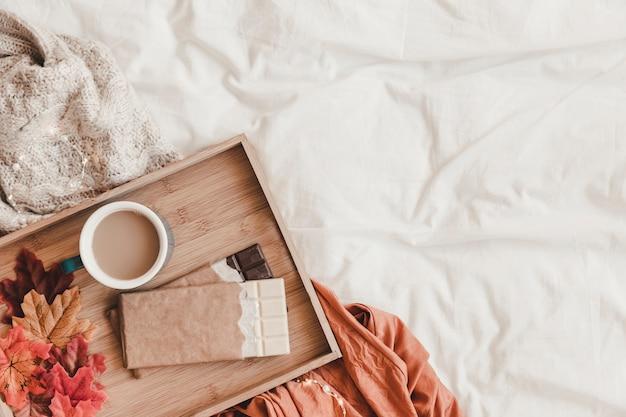 Chocolade en bladeren in de buurt van koffie op bed