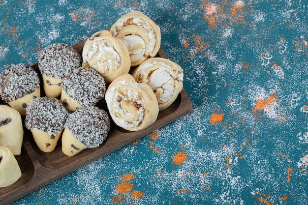 Chocolade en boterkoekjes in een vierkante houten plank.