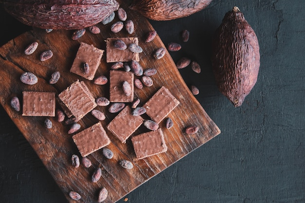 Chocolade en cacaobonen met cacao op een zwarte achtergrond