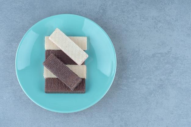 Chocolade en karamel wafel plakjes op blauw bord.