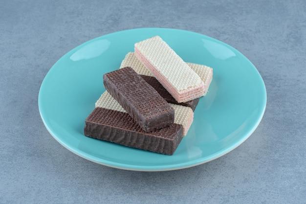 Chocolade en karamelwafeltjes op groene plaat over grijs.