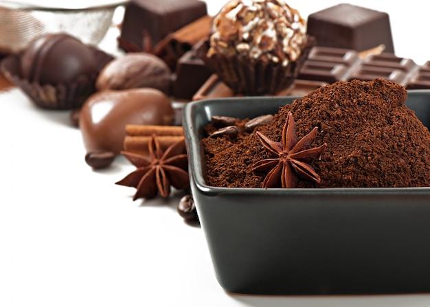 Chocolade en kruiden op witte oppervlakte wordt geïsoleerd die