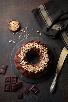 Chocolade en pompoenbundtcake met chocoladeglans en walnoot op donkere concrete achtergrond