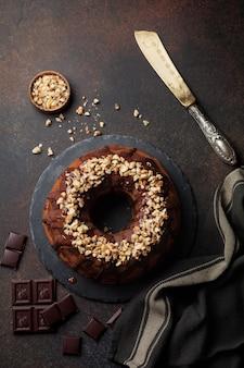 Chocolade en pompoenbundtcake met chocoladeglans en walnoot op donkere concrete oppervlakte
