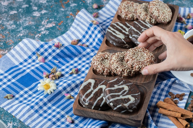 Chocolade- en sesamkoekjes op een houten bord.