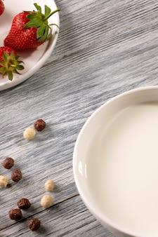 Chocolade en witte korrelballen met aardbeien en melkplaat op een grijze houten lijst met exemplaarruimte. bovenaanzicht