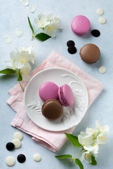 Chocolade en zwarte bessen franse macarons in keramische plaat op licht beton.