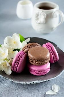 Chocolade en zwarte bessen franse macarons in keramische plaat op lichte betonnen tafel.