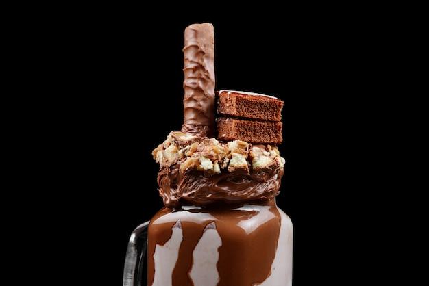 Chocolade extreme milkshake met brownie cake, chocopasta en snoep. gekke freakshake-voedseltrend. kopieer ruimte