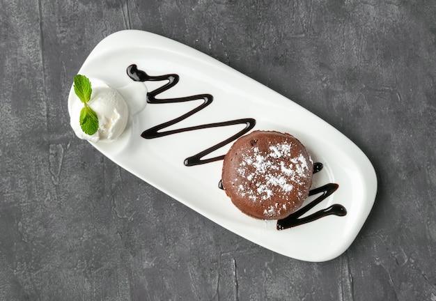Chocolade fondant met een bolletje ijs. gegarneerd met munt en chocolade topping. op een witte plaat. uitzicht van boven. grijze betonnen achtergrond.