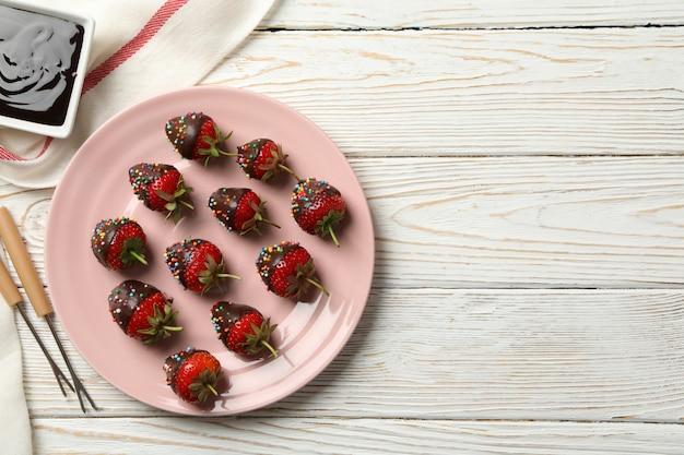 Chocolade fondue. aardbei in chocolade op witte houten achtergrond