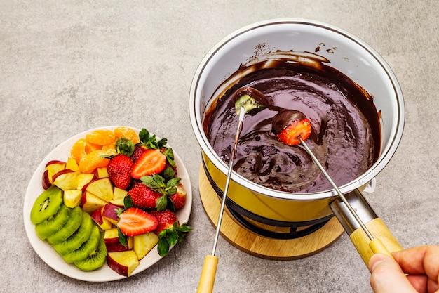 Chocolade fondue. geassorteerd vers fruit, twee soorten chocolade, mannelijke en vrouwelijke hand. ingrediënten voor het koken van een zoet romantisch dessert.