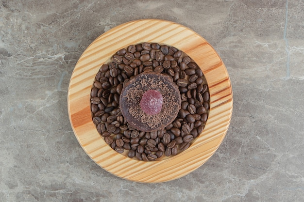 Chocolade frosted cake en koffiebonen op houten plaat