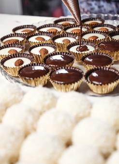 Chocolade ganache snoep met amandelen. gieten van chocolade, zelfgemaakt dessert.