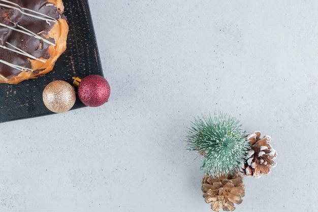 Chocolade gecoate cake op een bord naast kerst ornamenten op marmeren achtergrond.