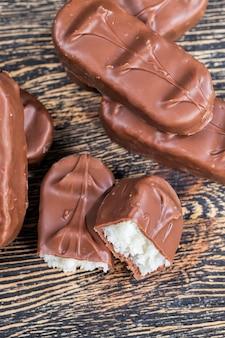 Chocolade gemaakt van cacao, suiker en melkpoeder, close-up van chocoladeproducten gemaakt van cacao en andere ingrediënten met een witte kokosvulling