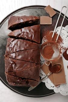 Chocolade gesneden cake met slagroom en cacaopoeder op ovenschaal over witte tafel