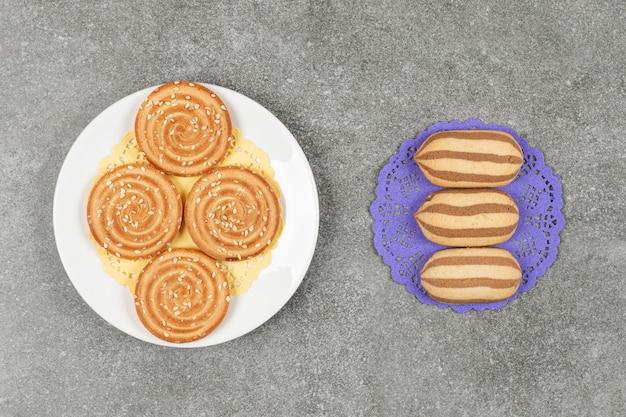 Chocolade gestreepte koekjes op blauw servet met plaat van sesamkoekjes
