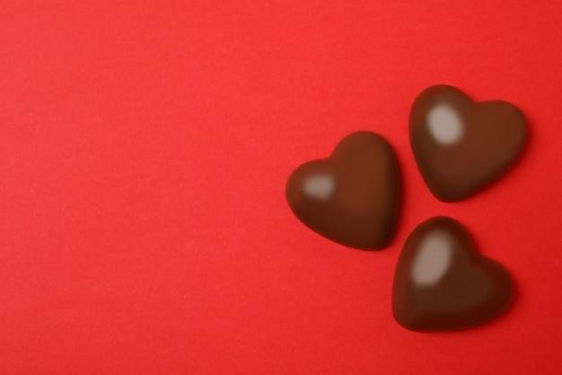 Chocolade hartjes op rode achtergrond, ruimte voor tekst