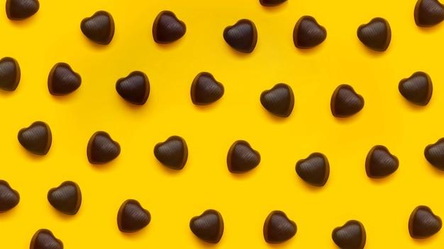 Chocolade hartvormige chocolaatjes op rode achtergrond op een rij. creatief patroon voor valentijnsdag. bovenaanzicht.