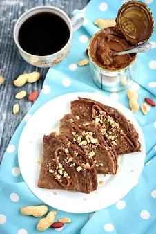 Chocolade haver pannenkoeken met karamel en noten op grijze houten tafel.