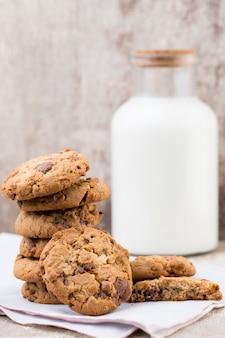 Chocolade havermout chip cookies met melk op rustieke houten tafel.