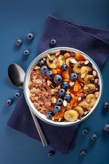 Chocolade havermoutpap met bosbes, noten, banaan, gedroogde abrikoos voor een gezond ontbijt. bovenaanzicht
