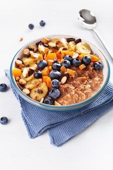 Chocolade havermoutpap met bosbes, noten, banaan, gedroogde abrikoos voor een gezond ontbijt