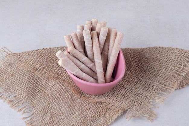 Chocolade hazelnoot pirouline wafel koekje in kom, op handdoek, op het marmer.