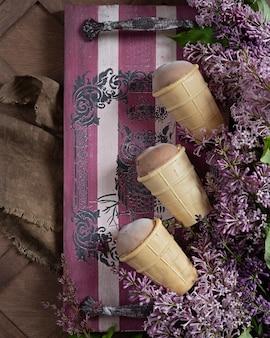 Chocolade-ijs in een wafel koppen op een houten dienblad en takken van lila