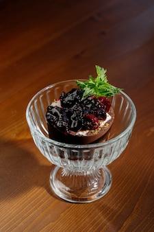 Chocolade-ijs met jam op tafel. chocolade-ijs met bessenjam in glazen beker