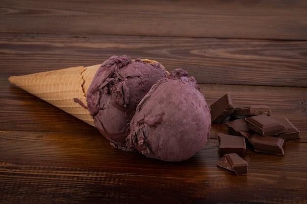 Chocolade-ijs scoops in wafel kegels en chocolade stukjes op houten achtergrond.