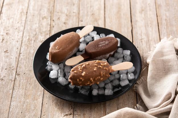 Chocolade ijslollys en gemalen ijs op zwarte plaat op houten tafel