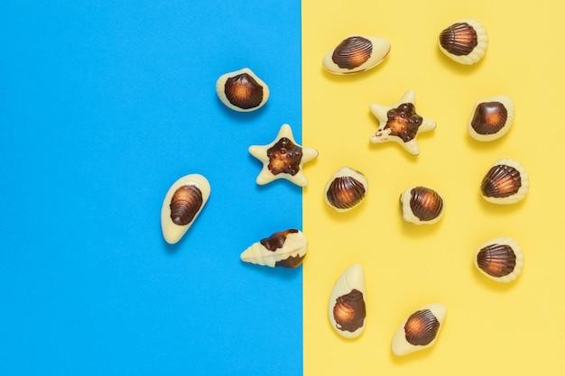 Chocolade in de vorm van schaaldieren en schelpen op een gele en blauwe achtergrond.