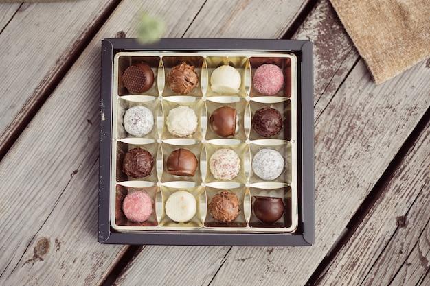 Chocolade in doos op houten ondergrond, zoet, snoep cadeau, bovenaanzicht