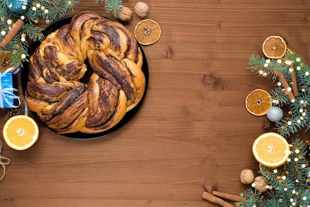 Chocolade kerst grootmoeder in de vorm van een krans met sinaasappelsiroop op een bord in stukjes gesneden. kerstversiering op een houten tafel.