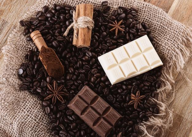 Chocolade, koffiebonen, anijs en kaneel op houten achtergrond