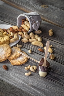 Chocolade lolly in de vorm van een klein kopje en diverse noten in een emmer op hout