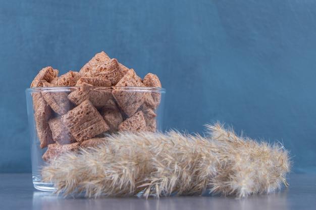 Chocolade maïs pads in een glas naast pampagras, op de blauwe achtergrond.