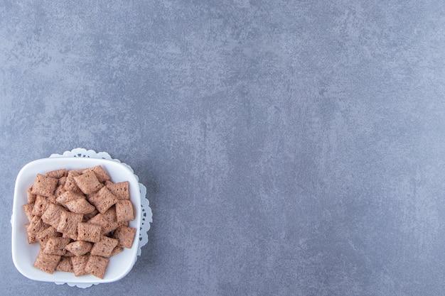 Chocolade maïs pads in kom op een onderzetter, op de blauwe achtergrond.