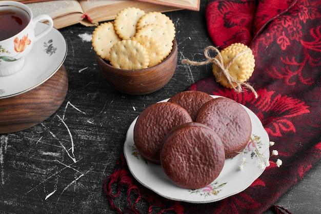 Chocolade marshmallow koekjes met een kopje thee en crackers.