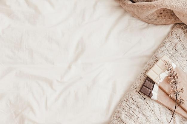 Chocolade met kruid en plaid liggend op witte bedsheet