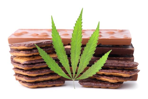 Chocolade met marihuana-extract, chocoladekoekjes met cbd-gehalte. chocoladerepen met noten en cbd-cannabisgehalte, groen hennepblad.