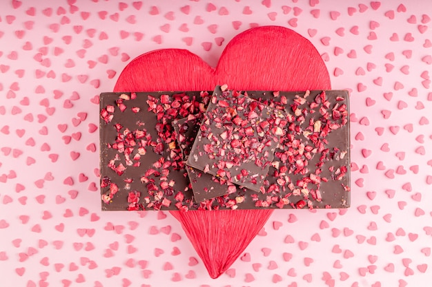 Chocolade met stukjes gedroogde bessen ligt een stapel op rood hart