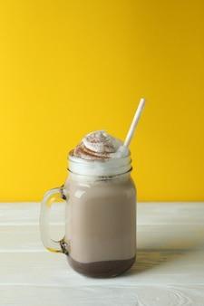 Chocolade milkshake op houten tafel tegen gele achtergrond