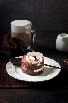 Chocolade minicake in elegante witte plaat en cappuccino met schuim in glazen beker op donkere achtergrond, bovenaanzicht. heerlijk dessert. ontbijttafel couvert.