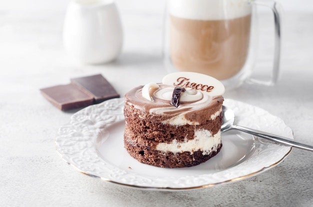 Chocolade minicake in elegante witte plaat en cappuccino met schuim in glazen beker op lichtgrijze achtergrond, bovenaanzicht. heerlijk dessert. ontbijttafel couvert.