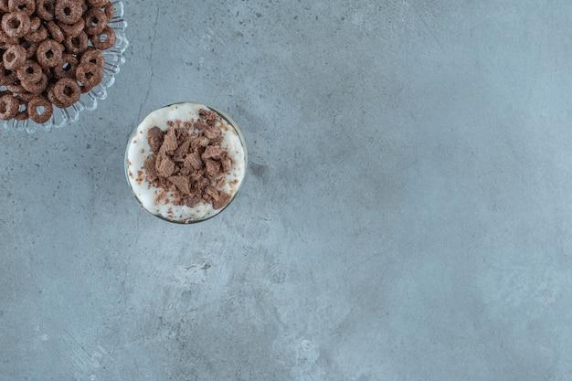 Chocolade mokka in een glas naast maïsring op een glazen voetstuk, op de blauwe achtergrond.