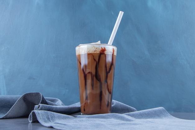 Chocolade mokka in een glas op stuk stof, op de blauwe achtergrond.
